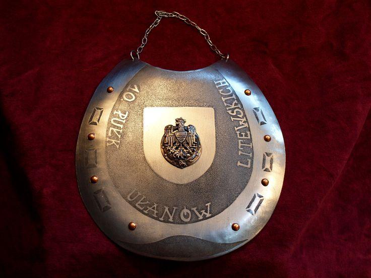 Ryngraf 10 Pułku Ułanów Litewskich.  Tarcza w kształcie podkutej podkowy (nawiązuje do odznaki), zamiast gwoździ miedziane nity.