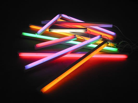 Flouro tubes are low power, can be painted or covered in gels and installed in cheap fixtures which can then be placed around a room. Very retro.