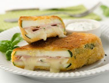 Für die Zucchini gefüllt mit Camembert die Zucchini in Längsrichtung in breite Streifchen schneiden und mit Pfeffer würzen. Camembert in dünne
