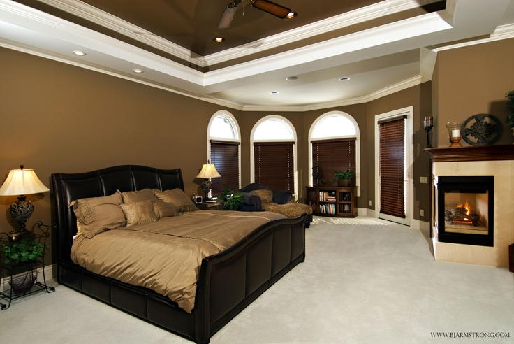 Luxurious master bedroom suite with 2 sided fireplace custom crown molding trey ceiling and Master bedroom with fireplace images