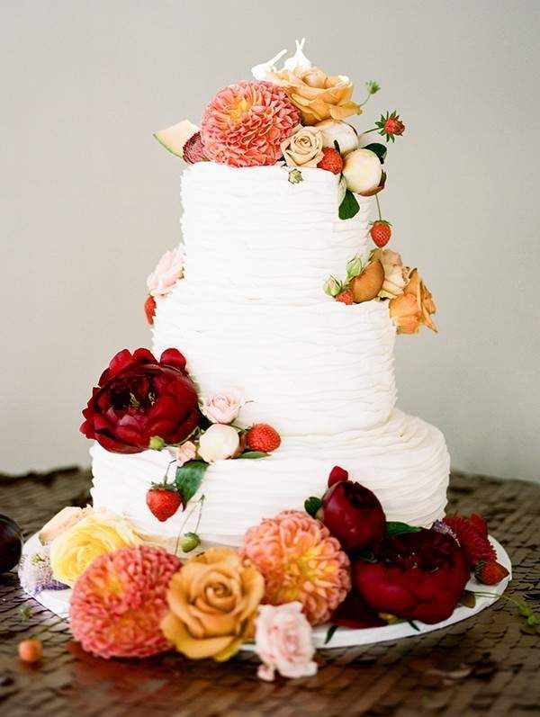 This tiered white wedding cake with a flower and fruit cake topper from the mywedding magazine is insane. So pretty!