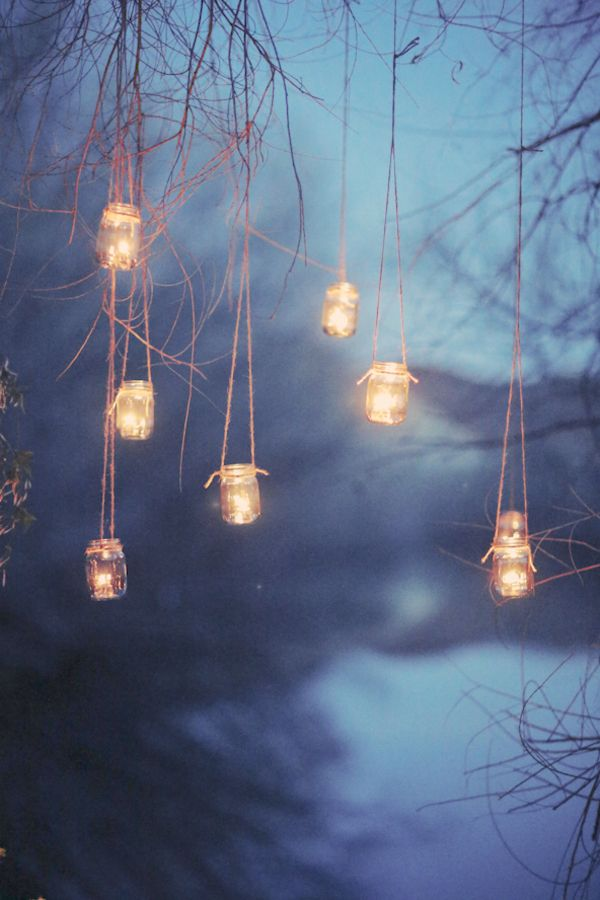 for that outdoor twilight wedding, candles in glass suspended from the trees are like fancy fireflies