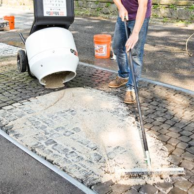 spreading grout onto a cobblestone driveway apron with a squeegee