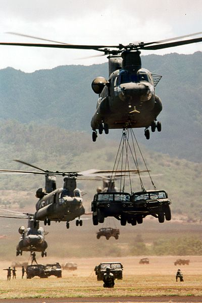 Boeing CH-47 Chinooks carrying military vehicles.