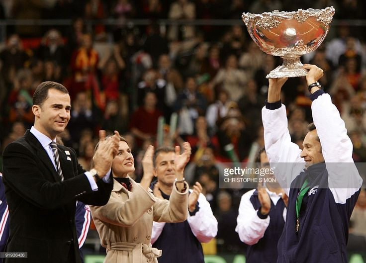 Spanish Davis Cup team captain Jordi Arrese (R) lifts the trophyy as Spanish Crown Prince Felipe (L) and his wife Princess Letizia (2ndL)applaud during the Davis Cup award ceremony, 05 December 2004 at La Cartuja Olympic stadium in Seville. Moya won the third single match 6-2, 7-6, 7-6 against Andy Roddick of the US to give Spain a 3-1 victory in the tie. Spain won his second ever Davis Cup title.