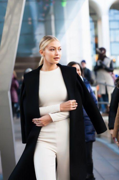 White jumpsuit with navy trench coat and sleek ponytail - Gigi Hadid street style