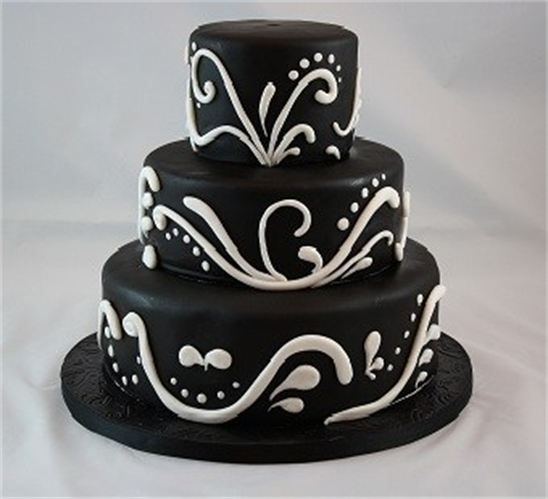 "Three tiers covered in black fondant decorated with white fondant scroll work for a ""classy and elegant 50th Birthday."" Cake flavors....coconut with island liqeuer buttercream; chocolate with vanilla buttercream and banana with banana buttercream."