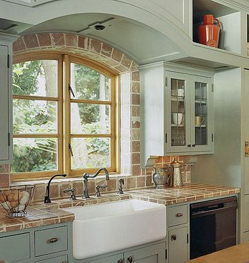 Marble Tile Backsplash          The tumbled marble kitchen backsplash and counters complement the barely-blue custom cabinets, gently arching window, and traditional apron-front sink.