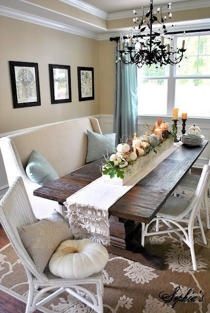 Elegant dining area with long wood table fabric bench wicker chairs black and crystal chandelier touches of light aqua blue white tand and black  shabby and cottage  pumpkin centerpiece
