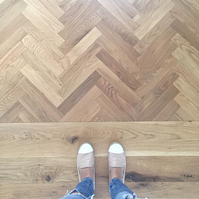 Herringbone white oak wood floors stained a custom blend of Minwax driftwood and pickled oak.