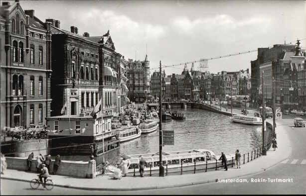 1950's. View on the Rokin towards Muntplein in Amsterdam. On the water the canal touring boats of Rederij Kooij. On the left the Oude Turfmarkt. Rokin is a major street in the center of Amsterdam. Originally it was part of the river Amstel. The Rokin begins at Muntplein square and ends at Dam Square. In 1936, the part between Spui Square and Dam Square was filled in. On the remaining part of the water, canal boats are now moored. Photo Takken. #amsterdam #1950 #Rokin
