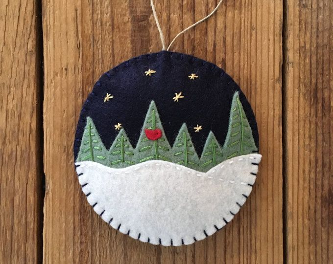 This ornament is handmade using a wool blend felt, Hemp cord, and is lightly filled using Polyfil. It measures approx. 3 3/4 in diameter. Ornament is entirely sewn by hand. Embroidery/design on one side only. Background felt is Navy blue in color.
