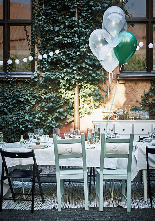 Buiten: lange tafel met stoelen en balonnen