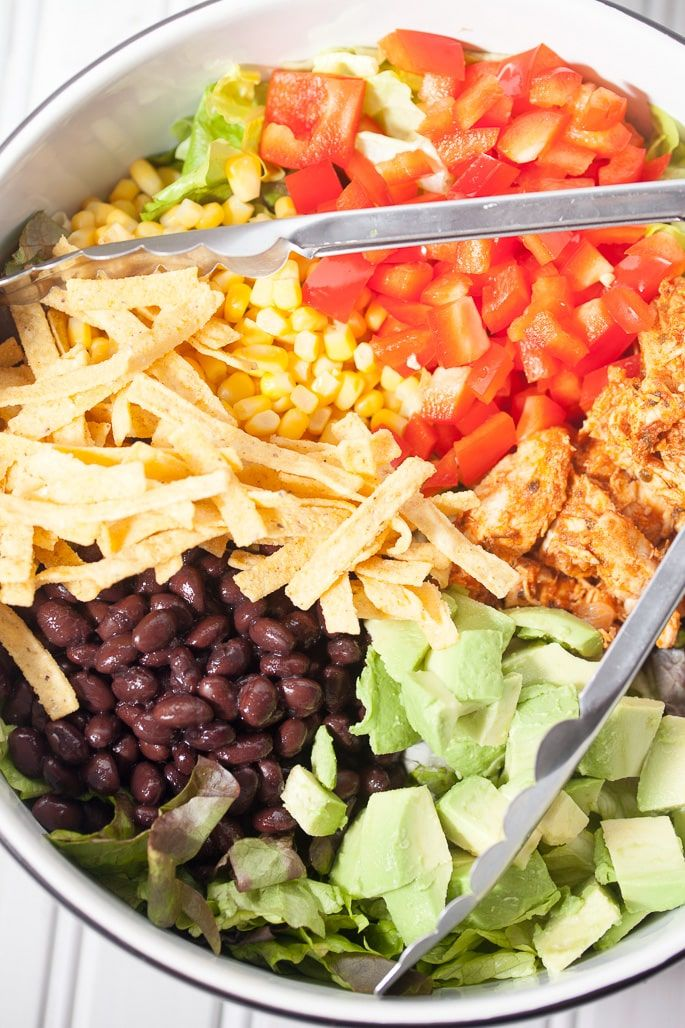 Shredded Chicken Taco Salad with Salsa Ranch-This wholesome salad is loaded with veggies like avocados, corn, and red bell peppers completed with crunchy tortilla strips, black beans, and a zesty homemade salsa ranch dressing. The shredded chicken is made completely from scratch and is so juicy and flavorful, this is a great weeknight meal that we love!