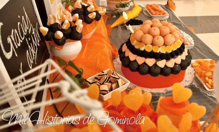 Candy bar o mesa de chuches con una paleta de colores en naranja, negro y blanco. Tarta de chuches y brochetas
