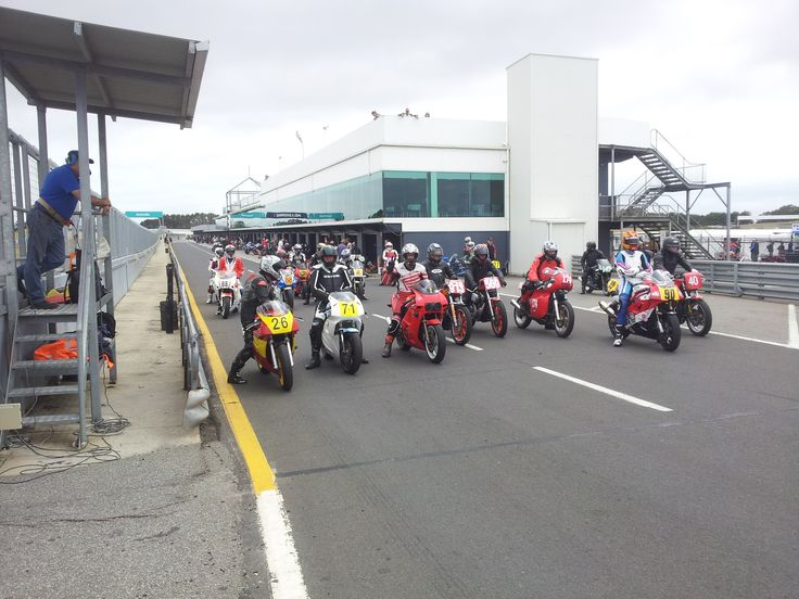 Phillip Island Grand Prix Circuit. Assorted Historic racing motorcycles waiting at Pit Exit - Island Classic 2015