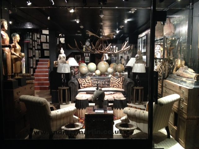 """Our new store front window on Walton Street in London.Shown is our """"Capulet chair"""", """"Horatio Bookcase"""" and """"Bobblili Stool. #andrewmartin #furniture #buddha #sidetables #sofa #vintage #decor #interiordesign #showroom #globes #london #black #design #style"""