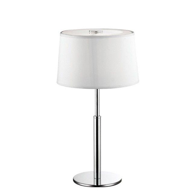 Lampada da tavolo Hilton Montatura in cromo. Paralume in lamina di PVC rivestita in tessuto. Sul fondo, diffusore in vetro trasparente sabbiato.