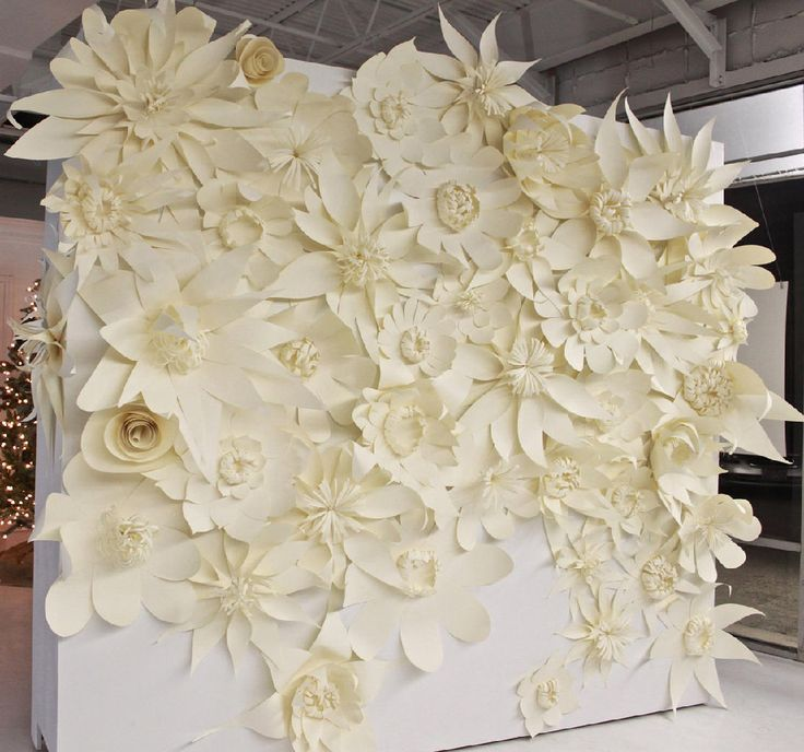 wedding backdrop - Huge white paper flowers pinned on the trees in an arch to form centered back drop