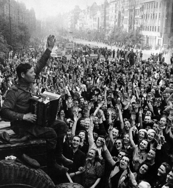 Soviet soldier with accordion in front of celebrating people after the liberation of Prague, May 1945