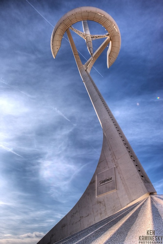 The Montjuic Communications Tower (Torre Telefónica) is a telecommunication tower in the Montjuïc  neighborhood of Barcelona, Spain. Designed by Santiago Calatrava, construction on the tower began in 1989 and was completed in 1992. The white tower was built for Telefónica to transmit television coverage of the 1992 Summer Olympics Games in Barcelona. The 136 m (446 ft) tower is located in the Olympic park, and represents an athlete  holding the Olympic Flame.