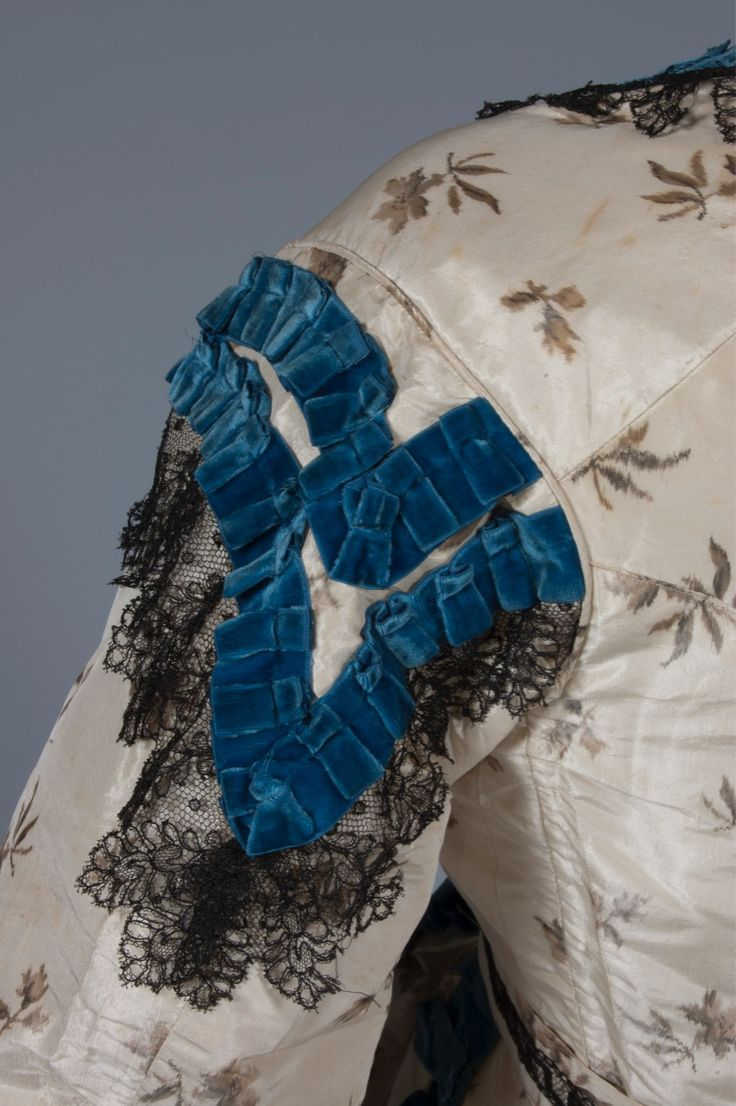 A sprigged chine taffeta gown, circa 1865, woven with small grey flowerheads, trimmed with blue velvet ribbon and black Chantilly lace, with separate bodice, belt and trained skirt. Being sold by Kerry Taylor Auctions for 350GBP.