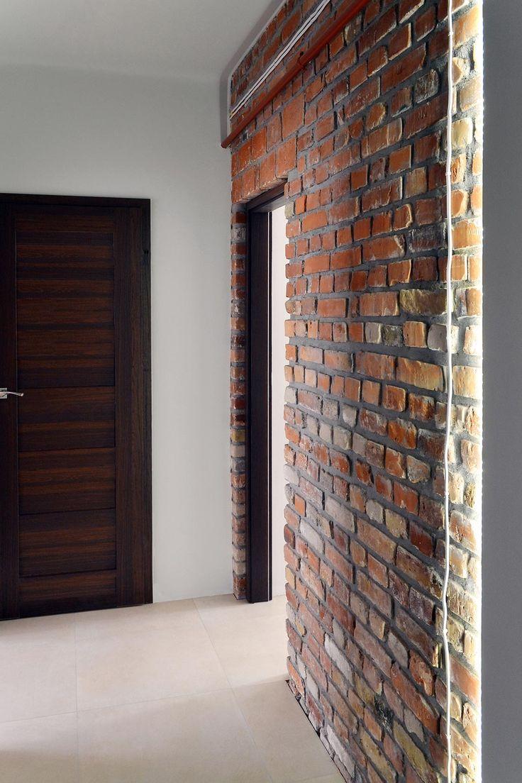 Ciemna stolarka drzwiowa pięknie współgra z surową cegłą. Zadbano o każdy detal. Rury pomalowano na kolor przygaszonej czerwieni.  | Maszroom.com