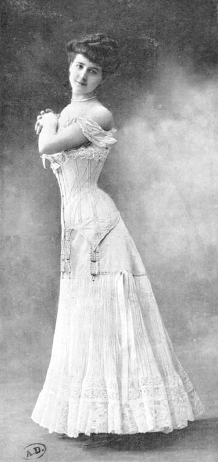 The style of this corset and the petticoat date both to around 1909-1910, certainly no later than early 1911. Corsets by 1909/10 had become slightly longer, the desired effect being to smooth the line in accordance with the newer, more columnar skirts. Toward 1910, as in this photo, petticoats (or 'combination' petticoats) were often worn under the corset, especially for day wear, not as the last piece of lingerie as in previous years.
