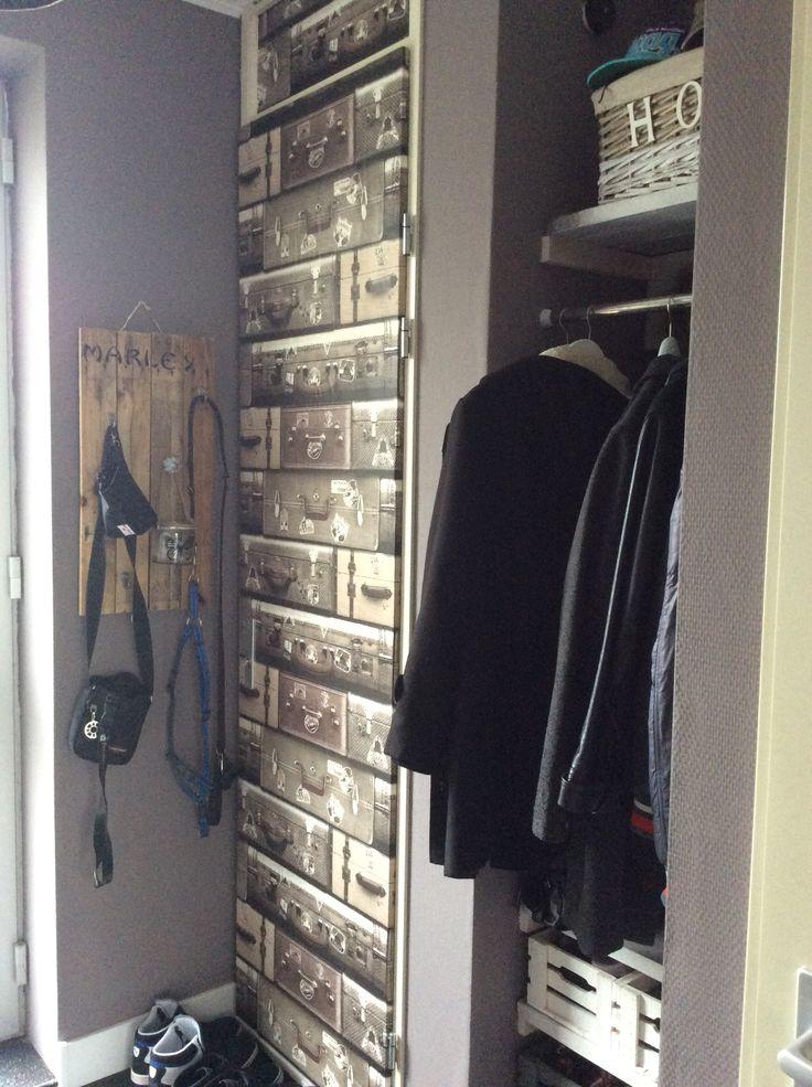 Meterkast deur in de gang behangen met vintage koffertjes