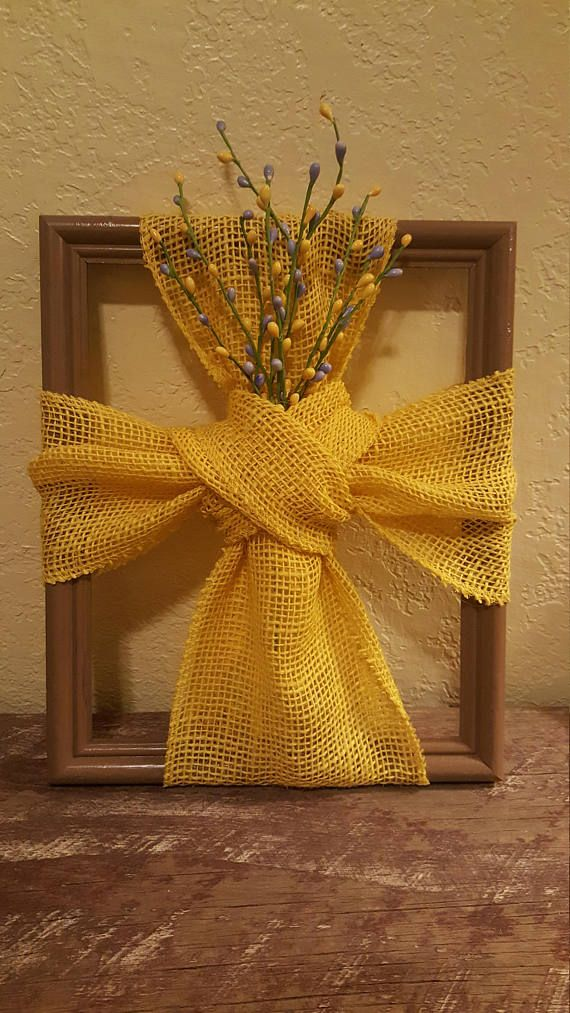 Wooden frame painted tan n wrapped with a yellow burlap cross around it. Purple n yellow beads added for a fun spring look