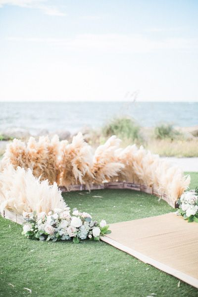 "An arch of flowers isn't the only way to dress up a ceremony location. For a recent bride who was wasn't a huge fan of blooms, Kehrin Hassan of Jet Set Wed and Sue Bain of Signature Florals combined forces to create this sophisticated, non-floral ceremony design. ""We created an intimate ceremony space by arranging dried Pampas grass, anchored in wooden boxes, in a small circle at the end of the aisle,"" says Hassan. Related: 100 Beautiful Outdoor Wedding Ceremonies"