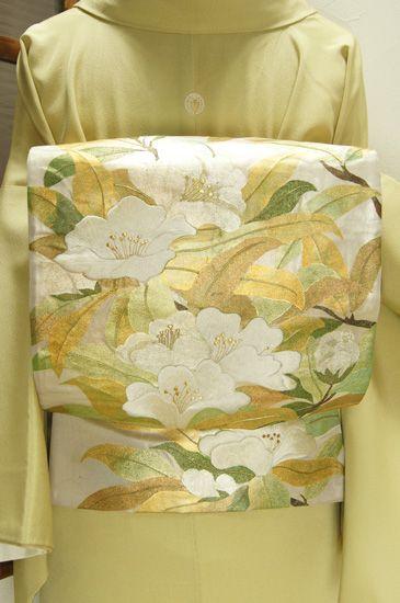 光の加減で幻想的に色を変える古味をおびた霞色のような銀色地に、ふっくらとした刺繍もぜいたくにあらわされた泰山木を思わせる白い花枝が美しい袋帯です。