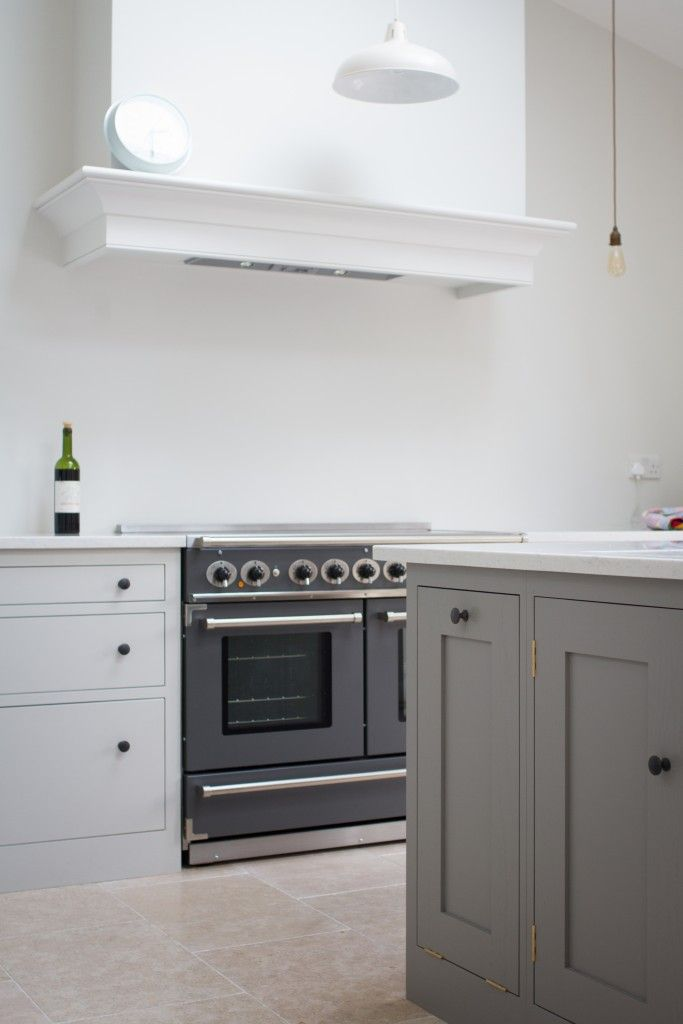 Sustainable Kitchens - Stunning Shaker Kitchen in London. Shaker style oak cabinets are painted in Farrow & Ball Strong White. The Falcon range cooker is visible with a cornice fitted around the extractor hood above. The island with oak worktop is painted in Farrow & Ball Mole's Breath.