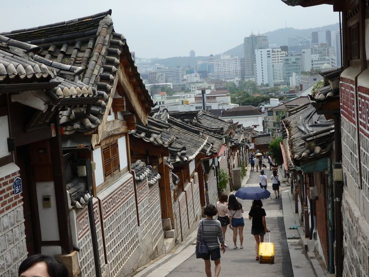 a view down a Buckchon Hanok Village street with the modern city in the background
