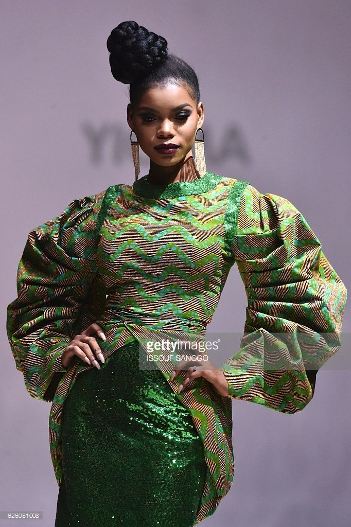 A model presents a creation by label Yioma during a fashion show marking the 170th anniversary of Dutch manufacturer of African luxury VLISCO in Abidjan on November 26, 2016. / AFP / ISSOUF
