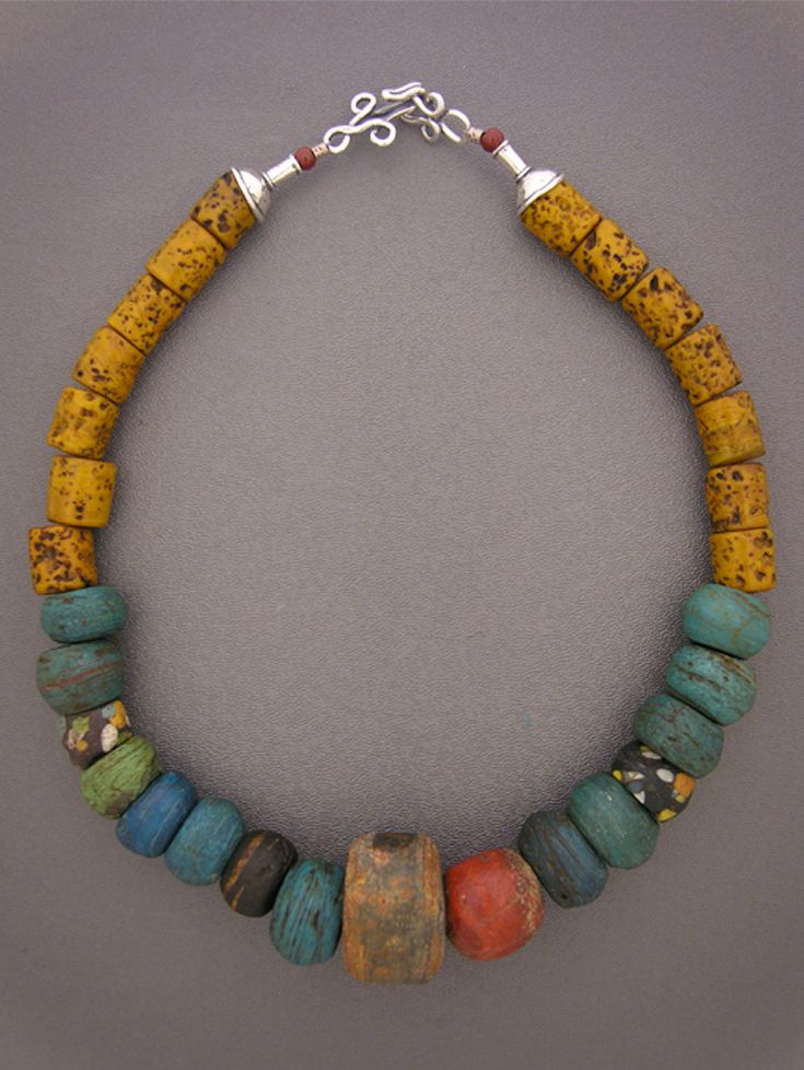 "by Anna Holland | Necklace; antique blue Hebron beads made in the Middle East from Dead Sea salts and sand (often traded in Africa), two collectible antique ""end of day"" beads, thought to be made from glass fragments cleaned up by beadmakers at the end of each day, a jasper bead, a large old stone bead, and amber/brown-colored pitted glass beads found in the Grand Bazaar in Istanbul. Silver cones and sterling silver hook and eye clasp 