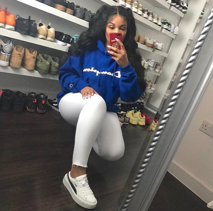 Instagram baddie in puma sneakers, white jeans, and a blue sweatshirt. Cute outfit for school or casual cool sneaker look.