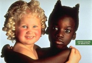 """Two innocent young girls — one white, one black — embrace one another.The girl on the left has the hair and cheeks of a cherub, of an angel. The other girl has her hair spiked up like devil horns and resists a smile. Although attempting a """"uniting"""" effect, the ad fails in its racist shortcomings, separating colors into good and evil."""
