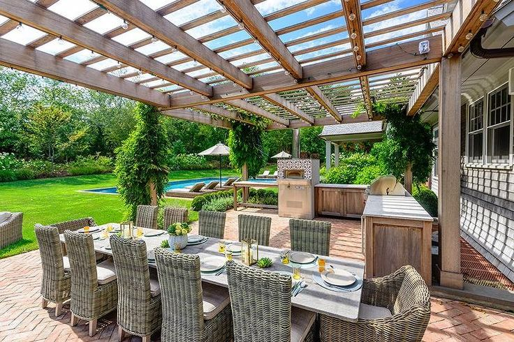 Fabulous patio features a pergola attached to the house shading an L shaped outdoor kitchen fitted with a pizza oven and bbq facing a rectangular concrete top dining table lined with wicker dining chairs atop a brick herringbone floor.