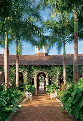 A cupola sits atop the entrance, which has arched doorways on axis with a tropical garden.  Dominican Republic, Robertson, of Cooper, Robertson & Partners,