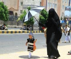 A mother holding an umbrella over her child. <3 #Niqabi