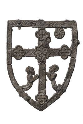 This is a pilgrim badge depicting Calvary (the site outside Jerusalem where Jesus Christ was crucified) from Gottsburen in Germany. The badge has a shield-shaped frame with a central cross and two kneeling figures at the base, all in openwork. The cross has a central star motif and quatrefoil terminals. There is the inscription 'INRI' across the top of the shield-shaped frame. There is a circular element projecting down from the top bar of the outer frame. 1450-1500 | Museum of London