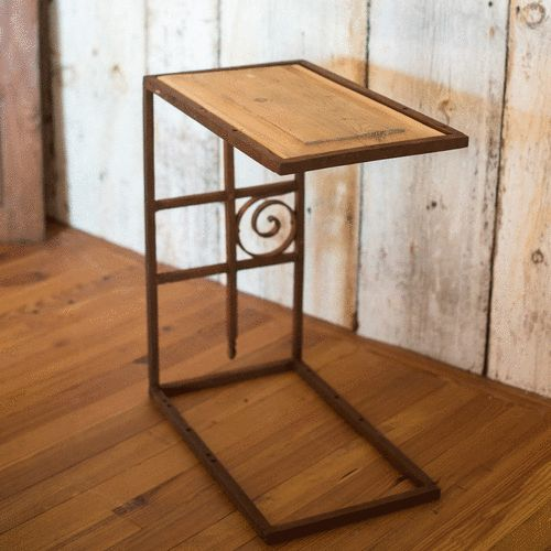 Graphic side table made of a salvaged wrought iron gate and a vintage wooden door pannel