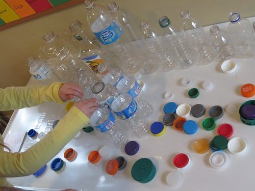 Bottle & Lid puzzle. She taped the bottles together to keep them from falling on the floor.