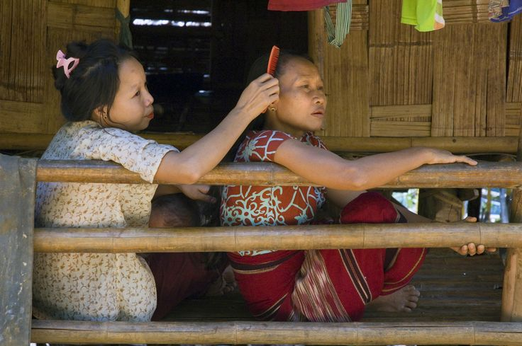 On International Women's Day, the United Nations High Commissioner for Refugees honours forcibly displaced women. Photo credit: Two Karen sisters relax on their front porch in Mae La Oon refugee camp in Thailand. UNHCR / J. Redfern / June 2006