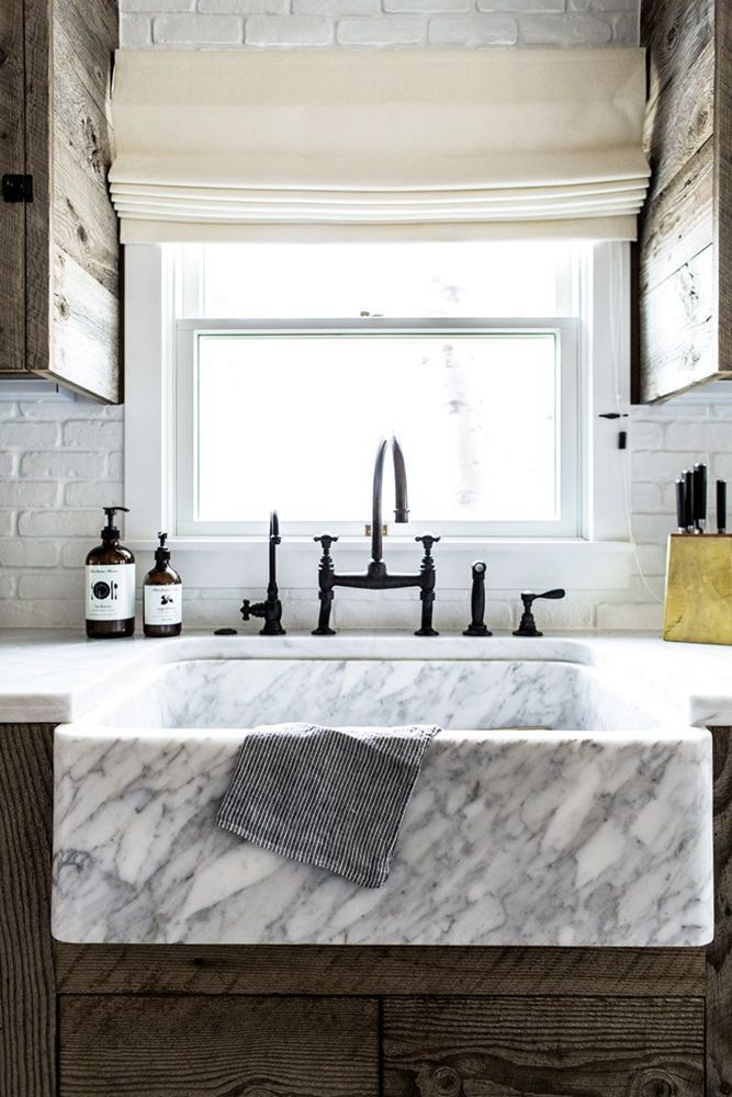 She lightened up the foundation with fresh additions like white wood paneling, bleached hardwood floors, and cabinetry covered in rustic reclaimed lumber.