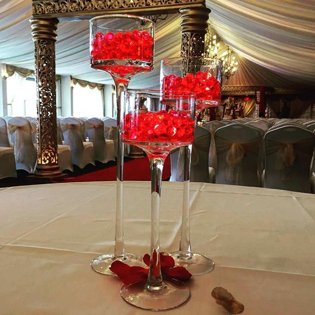 Trio of stemmed votives perfectly compliment the gold and red mandap. #indianweddingdecor #asianweddingideas #indianweddingeastmidland #weddingcenterpiece #redweddingdecor #hitenwedssonia