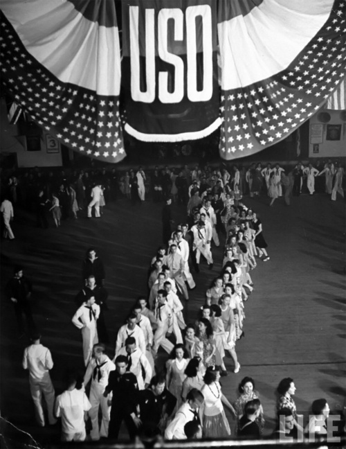 Men and women dancing a double conga line, winding its way through the vast hall of the City Auditorium at the USO in Virginia Beach, Virginia - 1942 ...