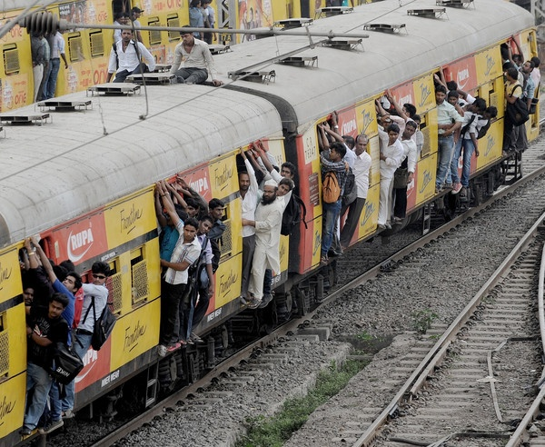 Commuters hang onto an overcrowded suburbun railway train on the Central Railway (CR) line in Mumbai . Two people were killed and around 10 were injured when they fell off a moving suburbun train on the CR line. Thousands of commuters in Mumbai had a harrowing time as services on the Central Railway line were thrown out of gear following a fire in a signal cabin between two suburbun railway stations on Tuesday night causing heavy damage to signalling gears. Mumbai's suburban trains or…