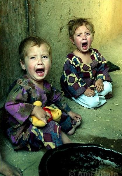 KABUL,AFGHANISTAN - SEPT. 12:  Fatima and Nadia, both orphans living at  the Shahad Nik Mohammed orphanage  in Kabul, Afghanistan cry September  12,2002. The children only had tea to drink this morning because there  was not even money for bread which costs about five cents a loaf. They  are living in desperate conditions as this country struggles to rebuild  itself. (Photo by Ami Vitale)